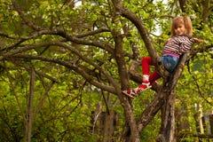 De stellende zitting van het meisje op een boom Stock Foto