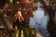 De stemming van de herfst Vele roze en magenta asters Jonge mooie vrouw die van de herfst in park in de herfst genieten Royalty-vrije Stock Fotografie
