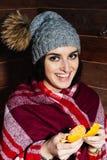 De stemming van de winter Jong mooi donkerharige die in kleren en GLB met mandarijnen op houten achtergrond glimlachen stock afbeeldingen