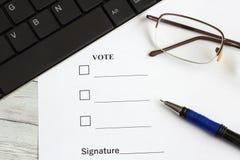 De stemmingsvorm op de bureaulijst dichtbij het toetsenbord, de pen en de glazen royalty-vrije stock foto's