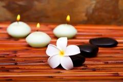De stenen van het kuuroord, kaarsen en frangipanibloem stock foto