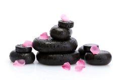 De stenen van het kuuroord met dalingen en roze bloemblaadjes Stock Fotografie