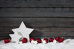 De ster vormde van Kerstmisbollen van de Kerstmisdecoratie de kaneelsterren op stapel van sneeuw tegen houten muur Stock Afbeelding