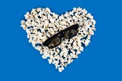 De stereoglazen liggen op het hart van popcorn Stock Fotografie