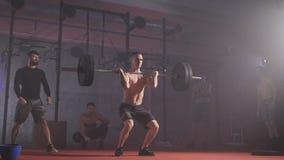 De sterke atleet fokt de bar met gewicht en houdt het stock videobeelden