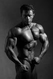 De sterke atletische mens toont mooi lichaam. royalty-vrije stock afbeeldingen