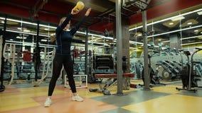 De sterke atletische vrouw die hurkzit met een kettlebell in haar doen dient langzame motie in stock videobeelden