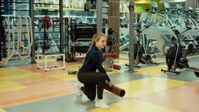 De sterke atletische vrouw doet hurkzit met een geschiktheidsbuis in gymnastiek in langzame motie stock videobeelden