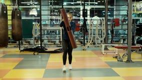 De sterke atletische vrouw doet hurkzit met een geschiktheidsbuis in gymnastiek in langzame motie stock video