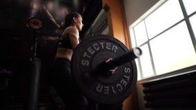 De sterke atletische vrouw voert schoon en pers in de gymnastiek in langzame motie uit stock video