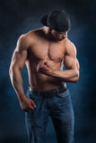 De sterke bodybuilder spant zijn krachtige spieren Stock Foto