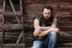 De sterke brutale mens met een baard en de tatoegeringen op zijn handen gekleed in leer bekleden en de jeans zit op een houten mu stock afbeeldingen