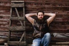 De sterke brutale mens met een baard en de tatoegeringen op zijn handen gekleed in leer bekleden en de jeans zit op een houten mu stock foto's