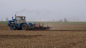 De sterke drank en maakt de grond op het gebied los alvorens te zaaien De tractor ploegt een gebied met een ploeg stock videobeelden
