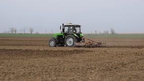 De sterke drank en maakt de grond op het gebied los alvorens te zaaien De tractor ploegt een gebied met een ploeg stock footage