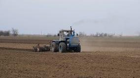 De sterke drank en maakt de grond op het gebied los alvorens te zaaien De tractor ploegt een gebied met een ploeg stock video