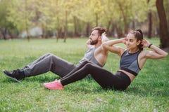 De sterke en krachtige mensen werken buitenkant in park uit Zij doen abs oefeningen De jonge man en de vrouw kijken royalty-vrije stock foto's