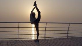 De sterke en mooie vrouw leunt op de dwarsbalk en warmt op Werpt haar benen over rug flexibiliteit kust stock video