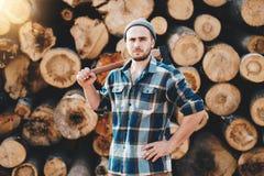 De sterke gebaarde houthakker die plaidoverhemd dragen houdt bijl op zijn schouder stock foto's