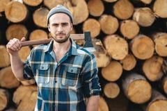 De sterke gebaarde houthakker die plaidoverhemd dragen houdt bijl op zijn schouder royalty-vrije stock afbeelding