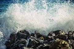 De sterke golf van overzees slaat op de rotsen stock fotografie