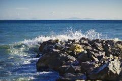 De sterke golf van overzees slaat op de rotsen royalty-vrije stock afbeeldingen