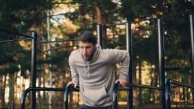 De sterke jonge mens doet tricepsonderdompelingen op brug in stadspark die in openlucht in de ochtend in de zomer uitoefenen stock video