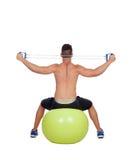 De sterke mens het praktizeren oefeningen met domoren zitten op een bal Stock Foto