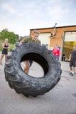 De sterke mens knipt zware band openlucht als training weg Stock Afbeelding