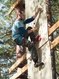 De sterke mens met een baard beklimt op rond de raad met haken op de achtergrond van bomen Royalty-vrije Stock Fotografie
