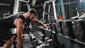 De sterke mens pompt spieren bij de gymnastiek, machtsoefeningen met domoren, atleet bij geschiktheidsclub, Kaukasische mens met stock videobeelden