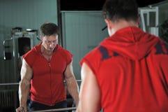 De sterke mens werkt in gymnastiek uit Royalty-vrije Stock Afbeeldingen