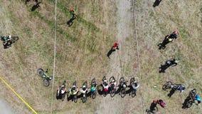 De sterke ruiters die van de bergfiets op het begin van ras in park wachten stock footage