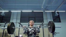 De sterke spiermens voert schoon en pers in crossfitgymnastiek in uit langzame motie stock video