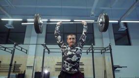 De sterke spiermens voert schoon en pers in gymnastiek in langzame motie uit stock video