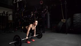 De sterke spiervrouw voert schoon en pers in crossfitgymnastiek in uit langzame motie stock videobeelden