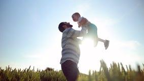 De sterke vader lobbed zoon in de hemel Het spelen met hem bij zonsondergang op het tarwegebied stock footage