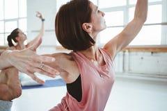 De sterke volwassen vrouw het praktizeren yoga stelt voor het handhaven van gezondheidszorg Groep actieve wijfjes die fithess uit royalty-vrije stock fotografie