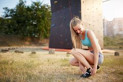 De sterke vrouw die van de rotsklimmer bij het beklimmen van schoenen zetten terwijl het zitten op gras Het vrij gezonde slanke m Royalty-vrije Stock Fotografie