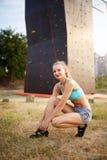 De sterke vrouw die van de rotsklimmer bij het beklimmen van schoenen zetten terwijl het zitten op gras Het vrij gezonde slanke m Stock Foto's