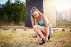 De sterke vrouw die van de rotsklimmer bij het beklimmen van schoenen zetten terwijl het zitten op gras Het vrij gezonde slanke m Royalty-vrije Stock Afbeelding