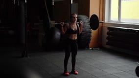 De sterke vrouw voert hurkzit met een barbell op ??n been in de gymnastiek in langzame motie uit stock video