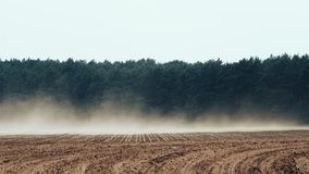 De sterke wind blaast rode grond van landbouwgrond stock videobeelden