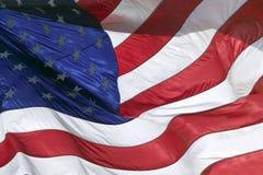 De sterren en de strepen, en de rode, witte en blauwe kleuren van een Vlag van de V.S. blazen in de wind Royalty-vrije Stock Afbeelding