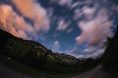 De sterrige hemel met vage motie kleurrijke wolken en helder maanlicht Expansief nachtlandschap in de Europese Alpen, fisheye u royalty-vrije stock foto's
