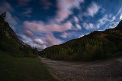 De sterrige hemel met vage motie kleurrijke wolken en helder maanlicht Expansief nachtlandschap in de Europese Alpen, fisheye u royalty-vrije stock afbeelding