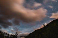 De sterrige hemel met vage motie kleurrijke wolken en helder maanlicht Expansief nachtlandschap in de Europese Alpen, fisheye u royalty-vrije stock fotografie