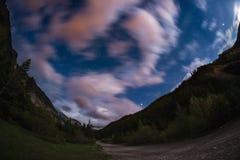 De sterrige hemel met vage motie kleurrijke wolken en helder maanlicht Expansief nachtlandschap in de Europese Alpen, fisheye u stock foto