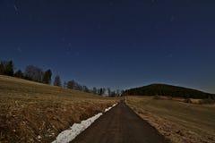 De sterrige nachthemel met ster sleept het roteren rond de Poolster boven één enkele steegweg die door gebieden leiden Stock Fotografie