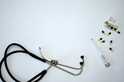 De stethoscoop, de elektronische thermometer en de gele pillen liggen op een witte achtergrond royalty-vrije stock foto